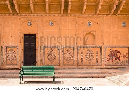 JAIPUR RAJASTHAN INDIA - MARCH 11 2016: Horizontal picture of green bench with painted wall inside of Nahargarh in Jaipur known as pink city of Rajasthan in India.