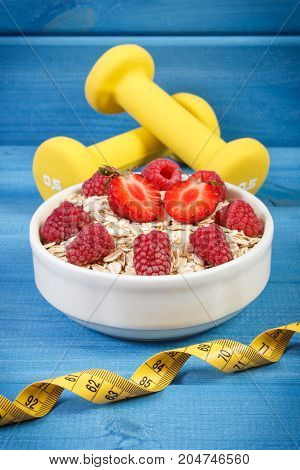 Oat Flakes Or Oatmeal With Fruits, Tape Measure And Dumbbells, Healthy, Sporty Lifestyle And Nutriti