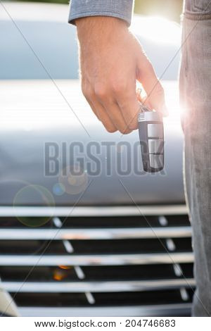 Cose-up of man holding keys to new car. Man's hand with new cars key. Copy space.