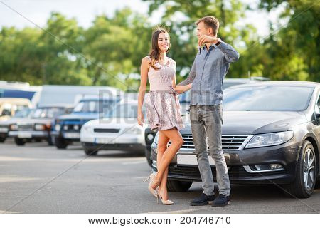 Beautiful couple is holding a key of their new car
