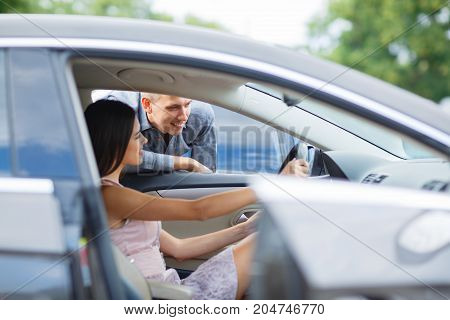 man buying a new car for his wife showing her something on the dashboard choosing automobile together at the dealership showroom