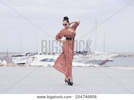 Young fashionable brunette woman wearing long dress in sunglasses posing near sea, pier with yachts