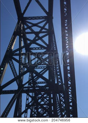 Top of old metal railroad bridge, now walking bridge for people on bright sunny day.