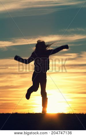 a child jumping at sunset in happiness.