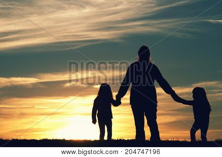 a mother walking with her children at sunset.