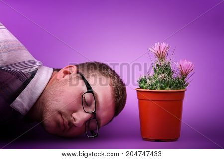 The man in glasses lies next to a small cactus in a red penny and gently pink flowered, isolated on a pink background. Lovely plant indoor. Cactus flower. Cactus in a plastic penny.