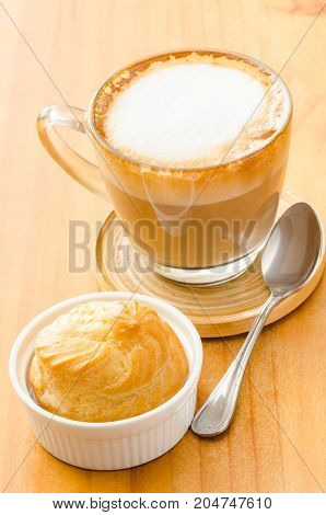 Cup of cappuccino and choux on wooden background