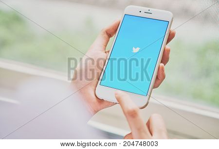 Bangkok Thailand - September 19, 2017 : Women using phone open Twitter application showing on screen an online social networking and service that enables users to send and read message