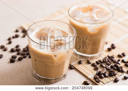 Glass of ice coffee with roasted coffee bean on wooden background