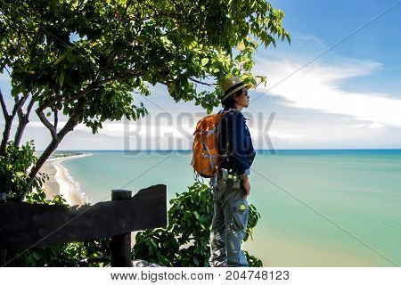 Man traveler with backpack and looking at tropical sea and beach in thailand