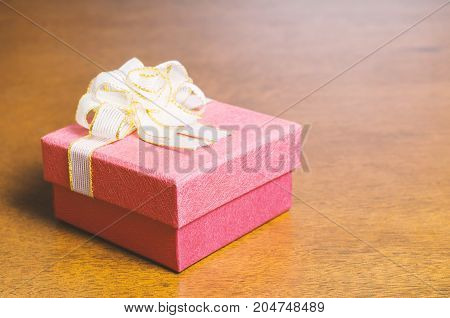 Red gift box decorated with golden ribbon on wooden background for giving in holidays