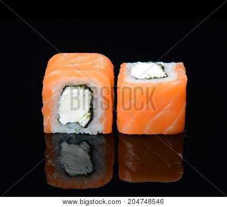 Philadelphia roll classic. Salmon, Philadelphia cheese, sushi on black background