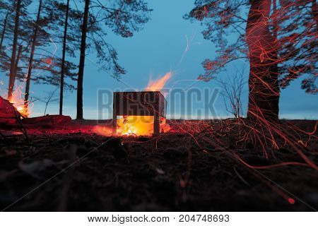 Burning firewood in the barbecue against the sky at night.