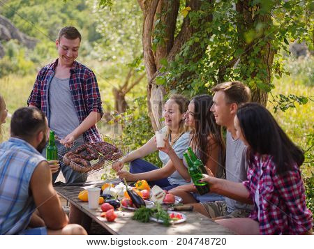 Young people having fun near the canyoun, drinking beers and chatting while their friends roast the meat on the bbq.