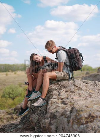 A beautiful couple is resting with a dog on a rock. Holidays in nature
