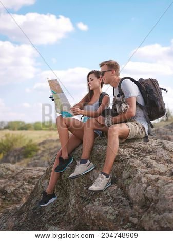 A young couple is looking for a road, looking at the map. Vacations in the fresh air with a dog. Healthy lifestyle