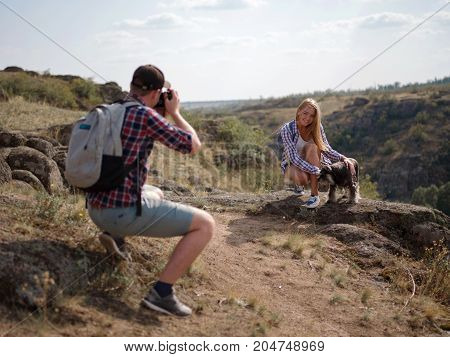 Young hipster guy taking photo of his girlfriend by using retro vintage camera. Love, travel and summer concepts.