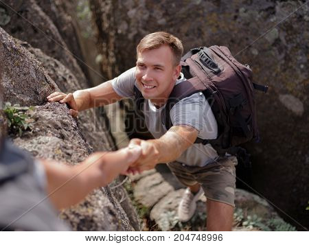 A young guy tries to climb to the top of the mountain to enjoy the view