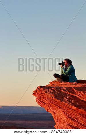 Page, Arizona - December 28, 2016: Female photographer takes pictures with big camera sitting on the edge of the cliff   at Horseshoe bend