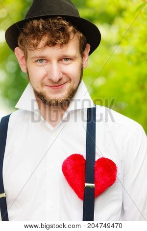 Love concept. Young fashionable man in hat retro style with red heart on chest