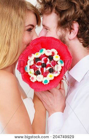 Loving couple kissing behind candy bunch bouquet flowers. Handsome man and pretty woman holding present gift. Relationship love concept.