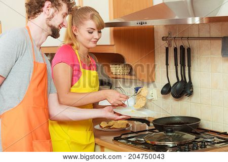 Couple woman and man in apron frying breaded chicken cutlet cooking preparing dinner food in kitchen together.