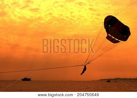 A silhouette of a parasailing on Pattaya beach.