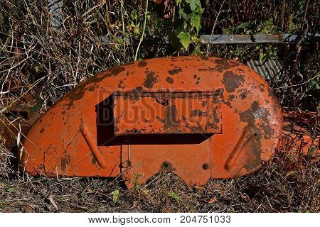 Old rusty orange tractor fender with an attached toolbox is left laying in the weeds and grass.
