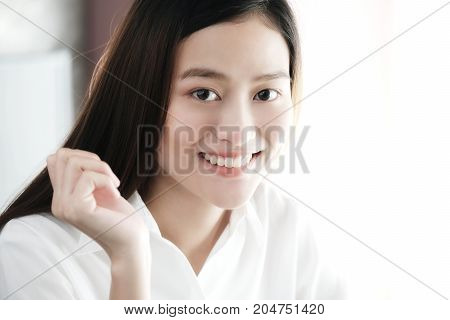 Portrait of smiling asian woman in white shirt and long hair close up