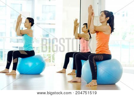 Group of young women stretching body on yoga balls in studio practice class wellness well being healthy lifestyle