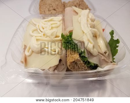 turkey sandwich with lettuce and mayonnaise in a plastic container