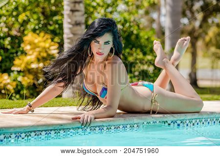 beautiful girl with long black hair lounging poolside