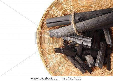 Charcoal in basket on white background. Free space for text