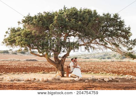 Newlywed couple sitting under shade of tree in summer.