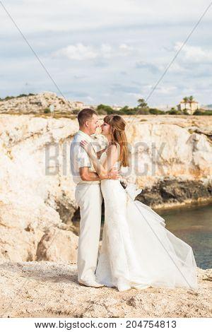 beautiful gorgeous bride and stylish groom on rocks