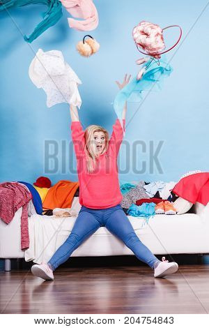 Woman Sitting On Messy Couch Throwing Clothes