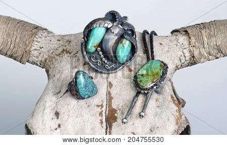 Antique Navajo sterling turquoise jewelry on top of cow skull.