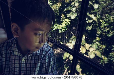 Asian Child Sitting Near Window And Looking Aside While Feeling Sad.
