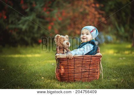 Happy little kid boy playing with bear toy while sitting in basket on green autumn lawn. Children enjoying activity outdoor. Childhood, baby, holiday, people, hobby concepts.