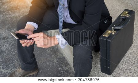 business man wearing black suit and using modern smartphone in outdoor.