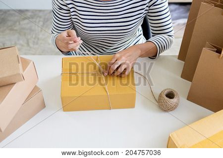Business owner woman working online shopping prepare product packaging process at her home young entrepreneur concept