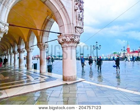 Venice, Italy - May 04, 2017: The people going near St Marks Square in Venice in Italy at raine day May 04, 2017