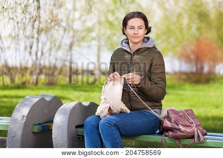 beautiful young dark-haired woman in a green jacket and jeans sitting on a bench and knitting with knitting needles from natural woolen threads a beige sweater in the park on a spring warm day in the background a grass