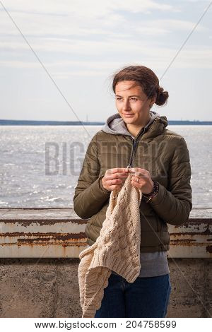 beautiful young dark-haired woman in a green jacket and jeans knits with knitting needles from natural woolen threads a beige sweater on the embankment near the river in a springy overcast day