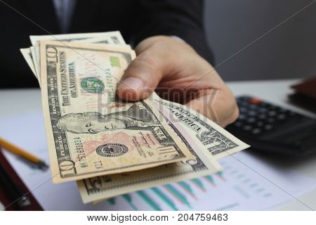 Pay the US dollar Hand use dollar money on the office desk investment and property for concept.