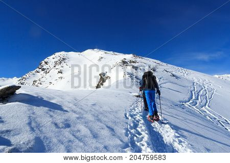 Group Of People Hiking On Snowshoes And Mountain Snow Panorama With Summit Cross In Stubai Alps, Aus