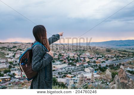 Young woman tourist with high point showing hand at sunset over the city of Goreme in Turkey. Tourism, vacation.