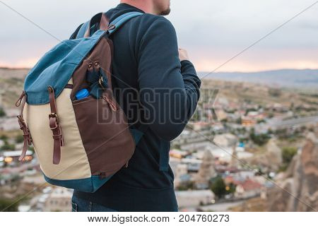 A tourist from a height looks at the sunset over a mountain town. Concept of tourism, hiking.