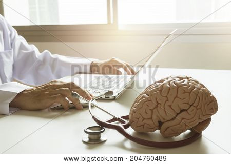 Doctor in neurology using laptop computer with stethoscope and brain model on the table