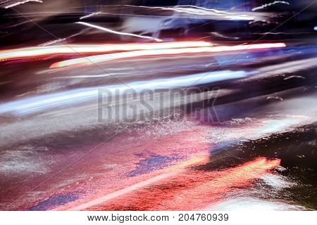 Blurred View Of Red Car Headlights As It Drives In Heavy Rain